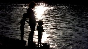 stock-footage-silhouette-mother-with-children-on-water